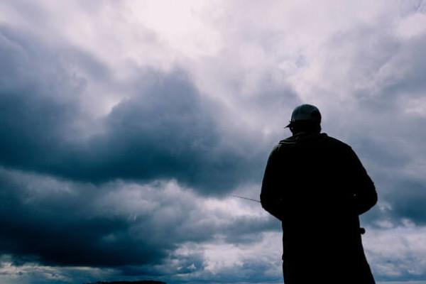 Fisherman Against Overcast Sky